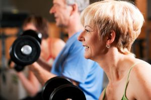 Fit older couple lifting wieghts.